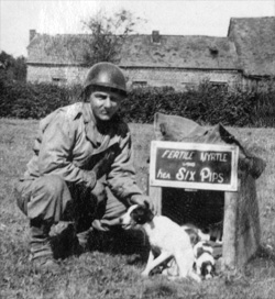 "Photo of Pfc ""Benny"" Benevento, 14th Chemical Maintenance Company, US Army, and company mascot dog ""Fertile Myrtle"" and her six puppies taken near La Capelle, France, mid-September 1944."