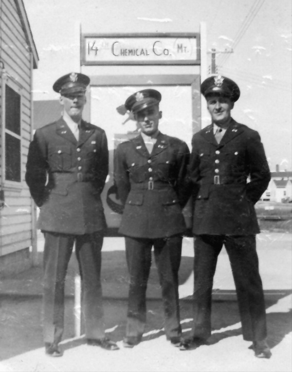 Photo of 1st Lt Arthur Schoenewaldt, 1st Lt Robert Marmorstein, 2nd Lt Walter Kovacs of 14th Chemcial Maintenance Company standing in front of company crest in their WW-II U.S. Army uniforms, at Camp Gordon, Georgia, circa October-November 1943