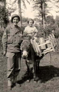 Photo of Staff Sergeant Herbert Landers of 14th Chemical Maintenance Company US Army WW-II and young French girl on a donkey taken circa the summer of 1944