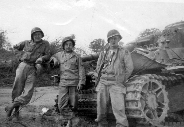 Photo of T/Sgt John Bogden, T/5 Harold A. Andrews, and Pfc William Long of 14th Chemical Maintenance Company, in their WW-II U.S. Army uniforms posing next to a wrecked German Panzer IV Type H tank, taken circa 05 August 1944 near St. Lo, France